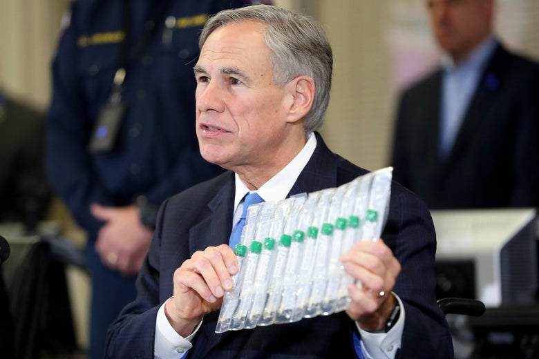 Greg Abbott, in a navy suit, holds up a clear plastic case containing several vials with green lids. Two men stand in the background.