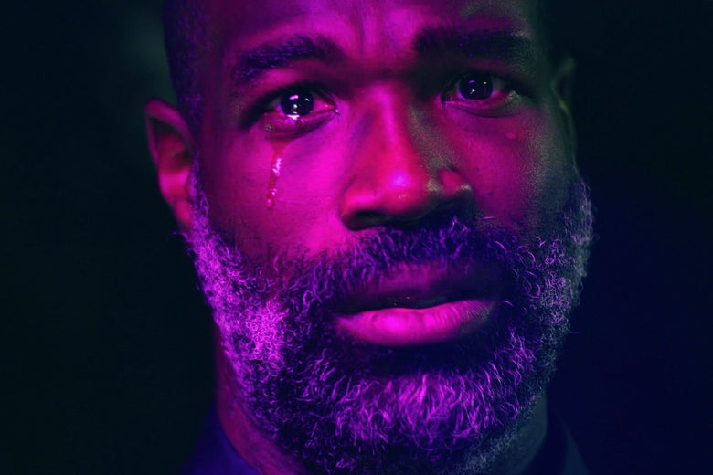 Tunde Adebimpe stares at the viewer, his face lit in neon, a tear running down his cheek