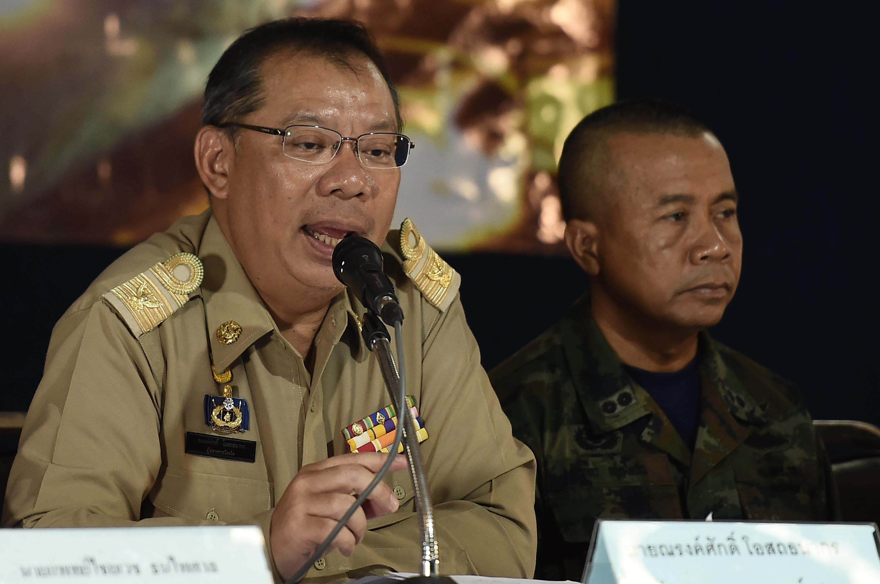 Narongsak Osotthanakorn, wearing glasses and a brown uniform, speaks into a microphone.