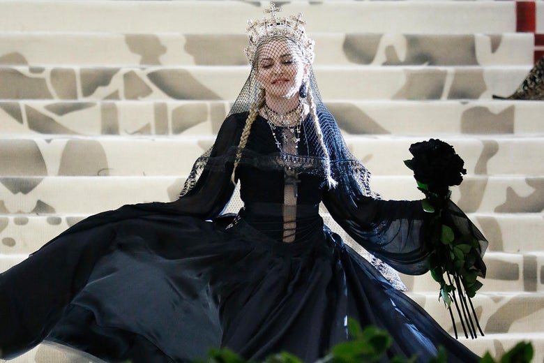 Madonna stands on the steps of the Met wearing a poofy black dress with multiple rosaries. She wears a crown made of crosses.