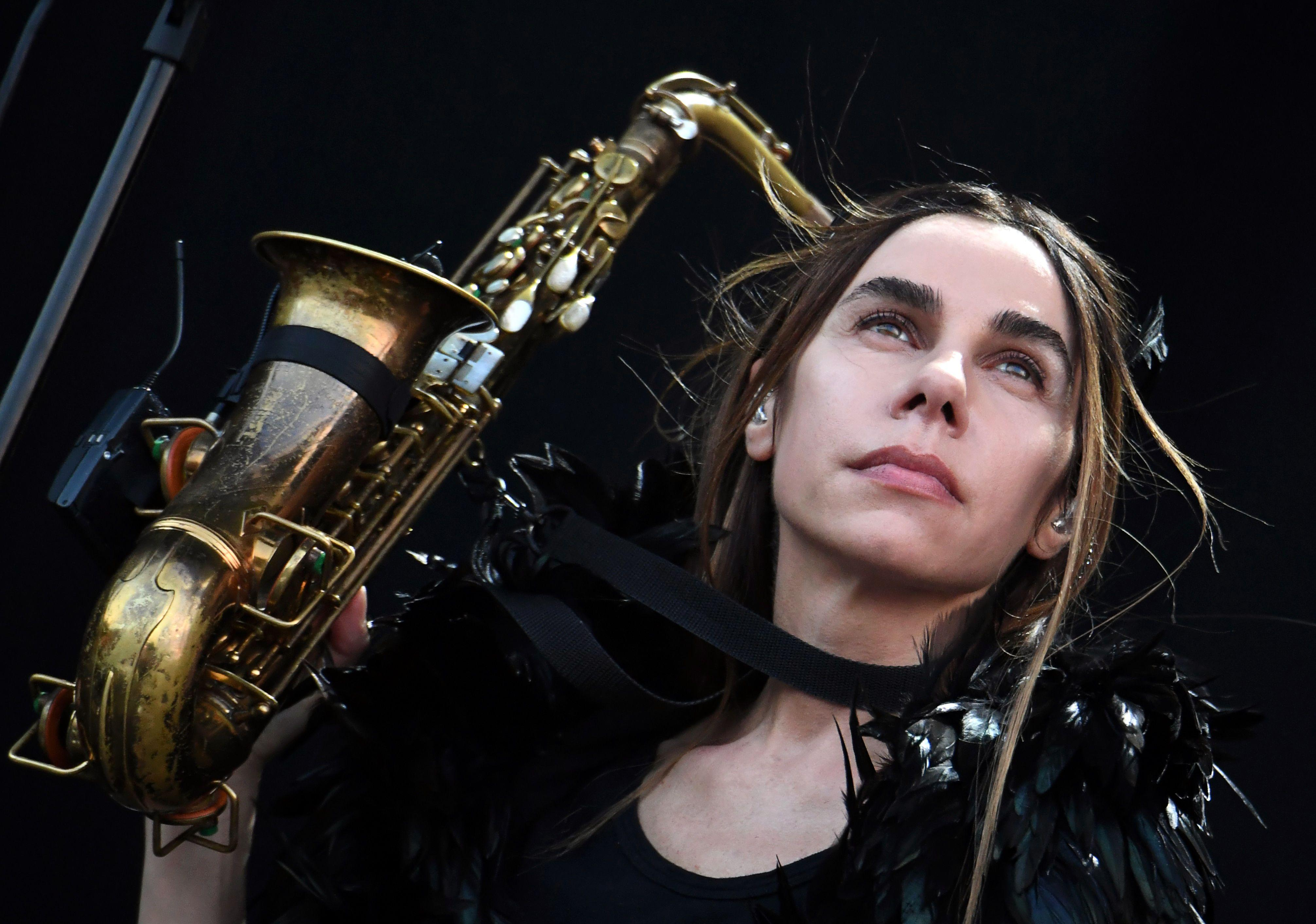 PJ Harvey, with an aloof stare and black-feathered get-up, holds a saxophone in front of a black background