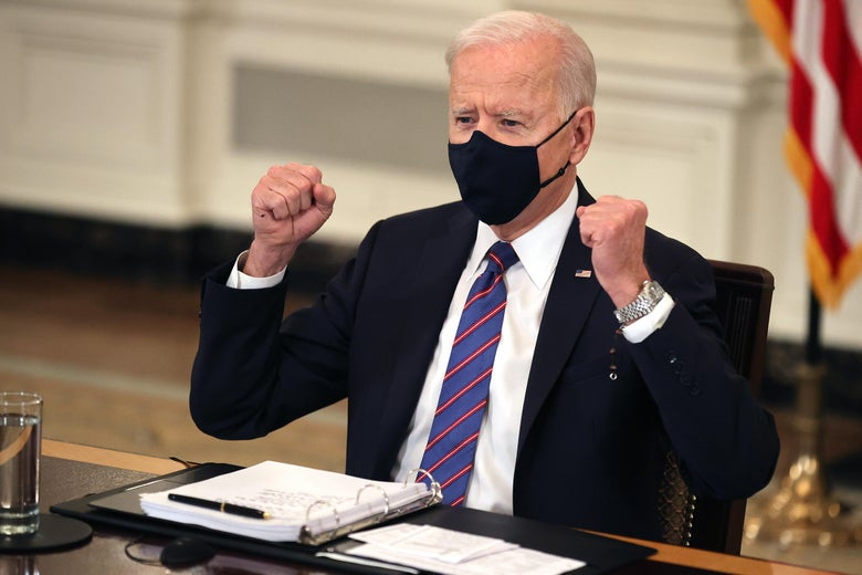 Joe Biden, wearing a face mask, sits at a table and raises his fists.