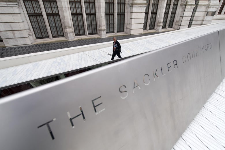 "A man can be seen walking behind a low wall that says, ""The Sackler Courtyard."""