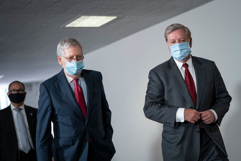 The two men, both wearing suits and blue masks, walk side by side in a hallway.