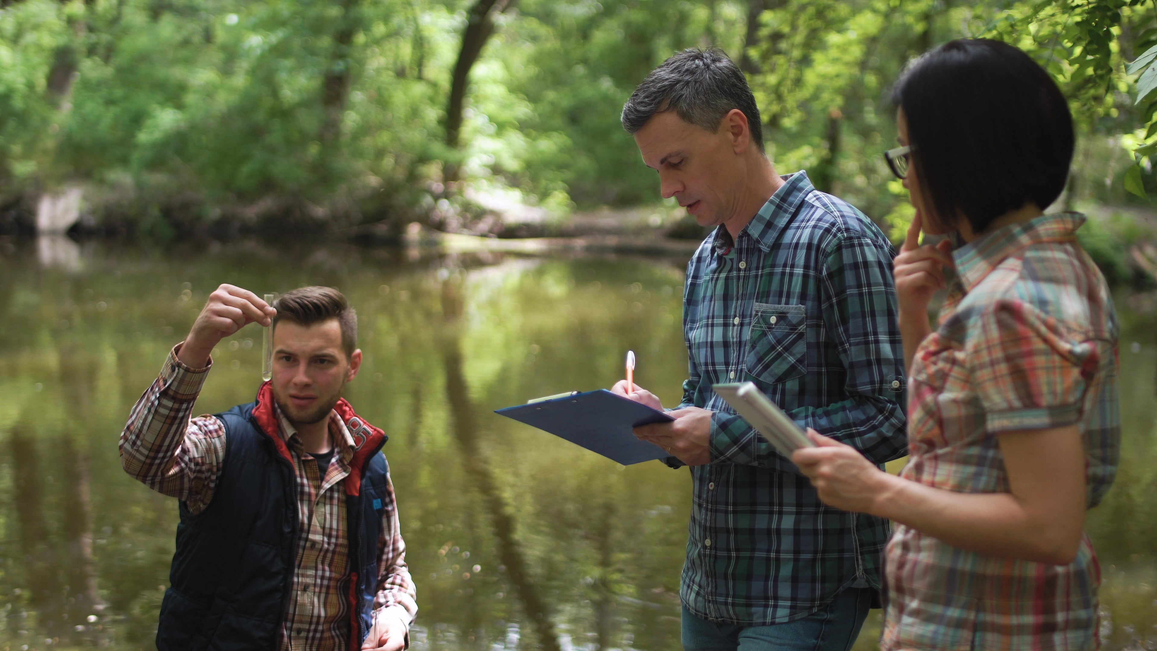 Three scientists analyze a water sample from a lake.