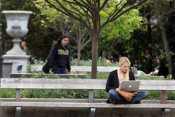 A UC Berkeley student works on her laptop while sitting on the UC Berkeley campus.