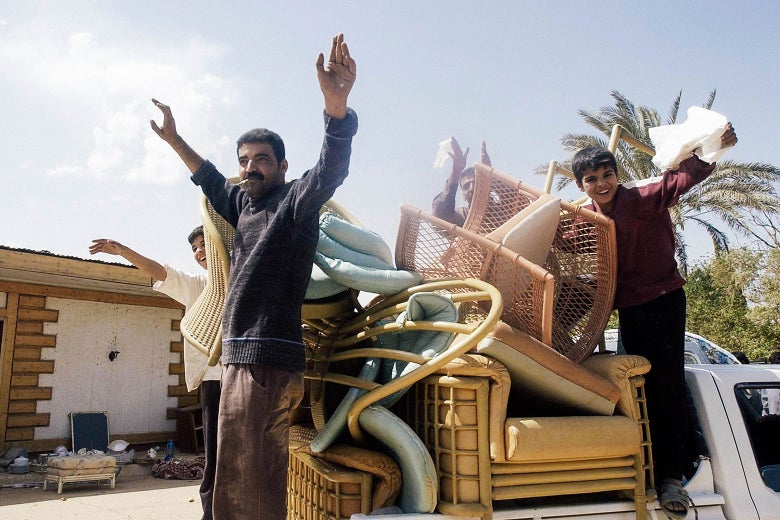 Iraqis stand in the back of a truck piled high with furniture.