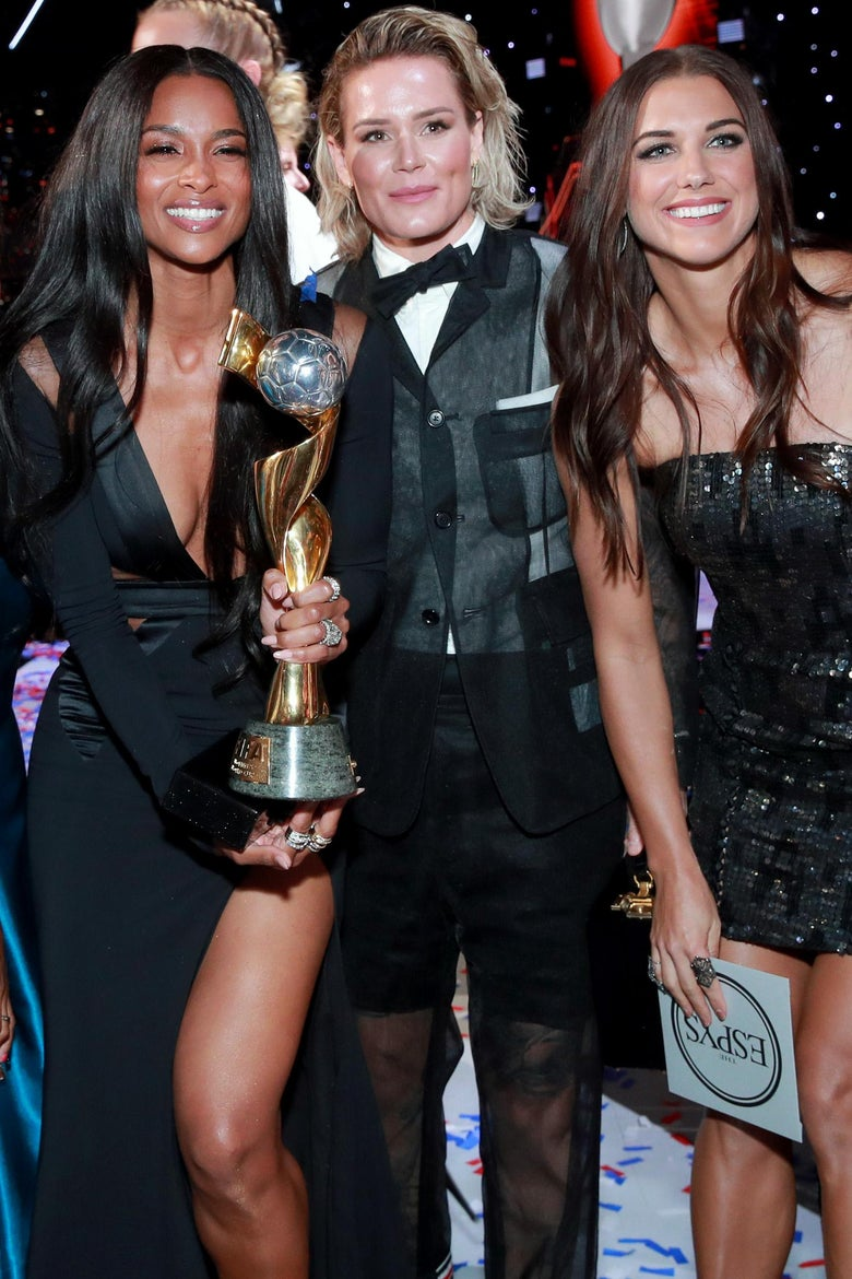 Ciara, Ashlyn Harris, and Alex Morgan pose and smile. Ciara holds the team's World Cup trophy.