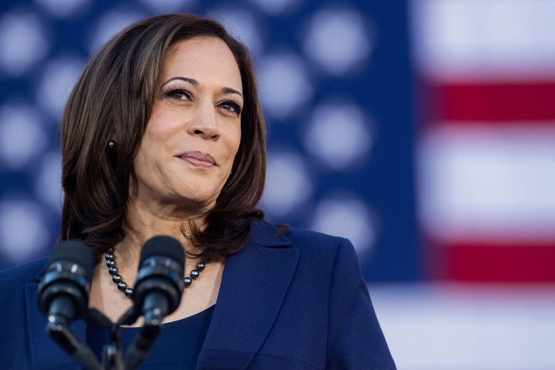 Kamala Harris standing at a mic in front of an American flag
