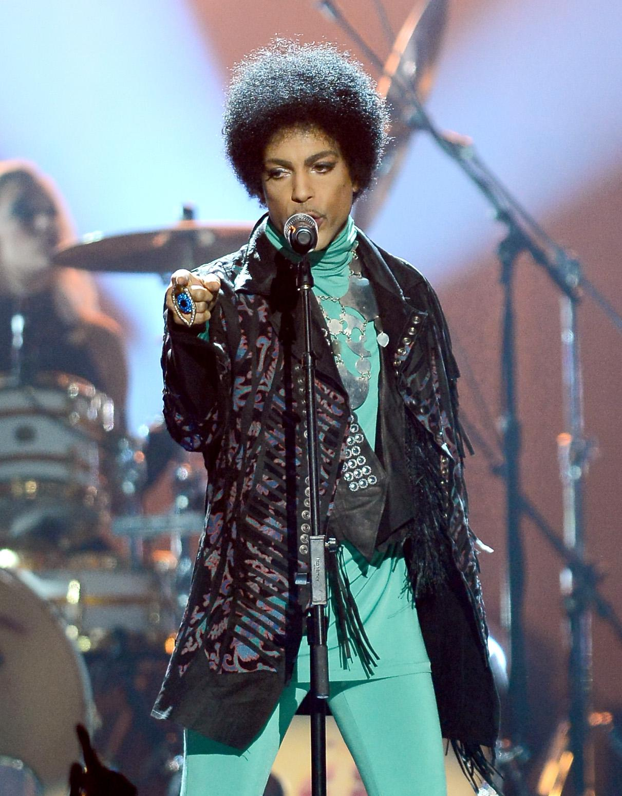 Prince stands in front of a microphone, points toward the camera.