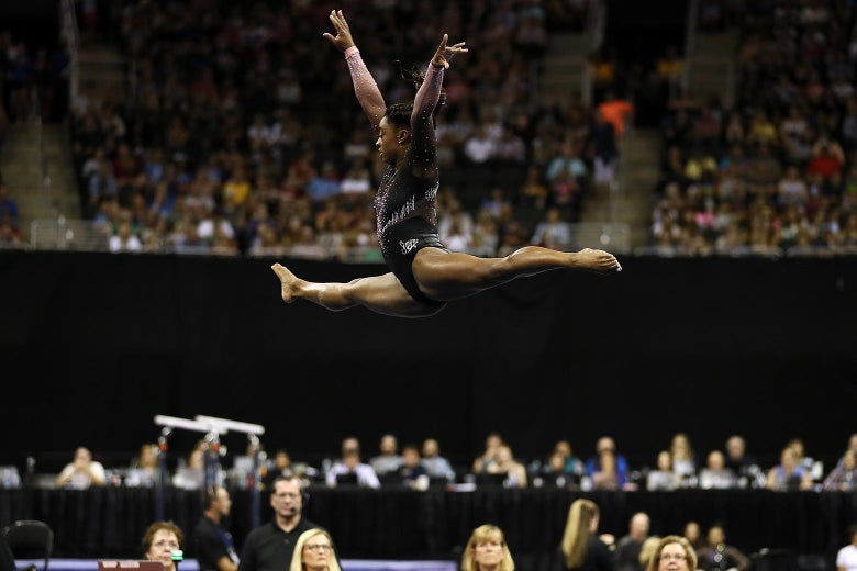 Simone Biles is seen mid-leap during her floor exercise on Sunday in Kansas City.