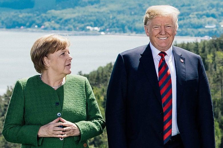 Angela Merkel looks at Donald Trump as he stares ahead smiling.