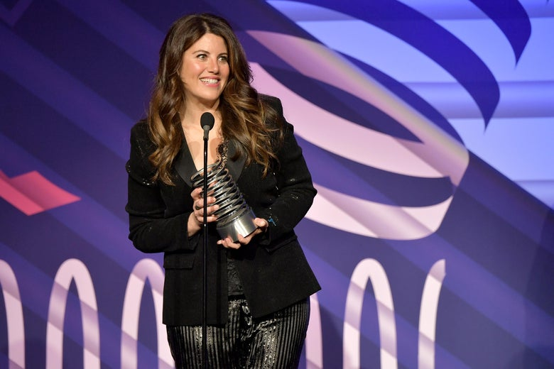 Monica Lewinsky stands on a stage in front of a microphone, holding a Webby award.