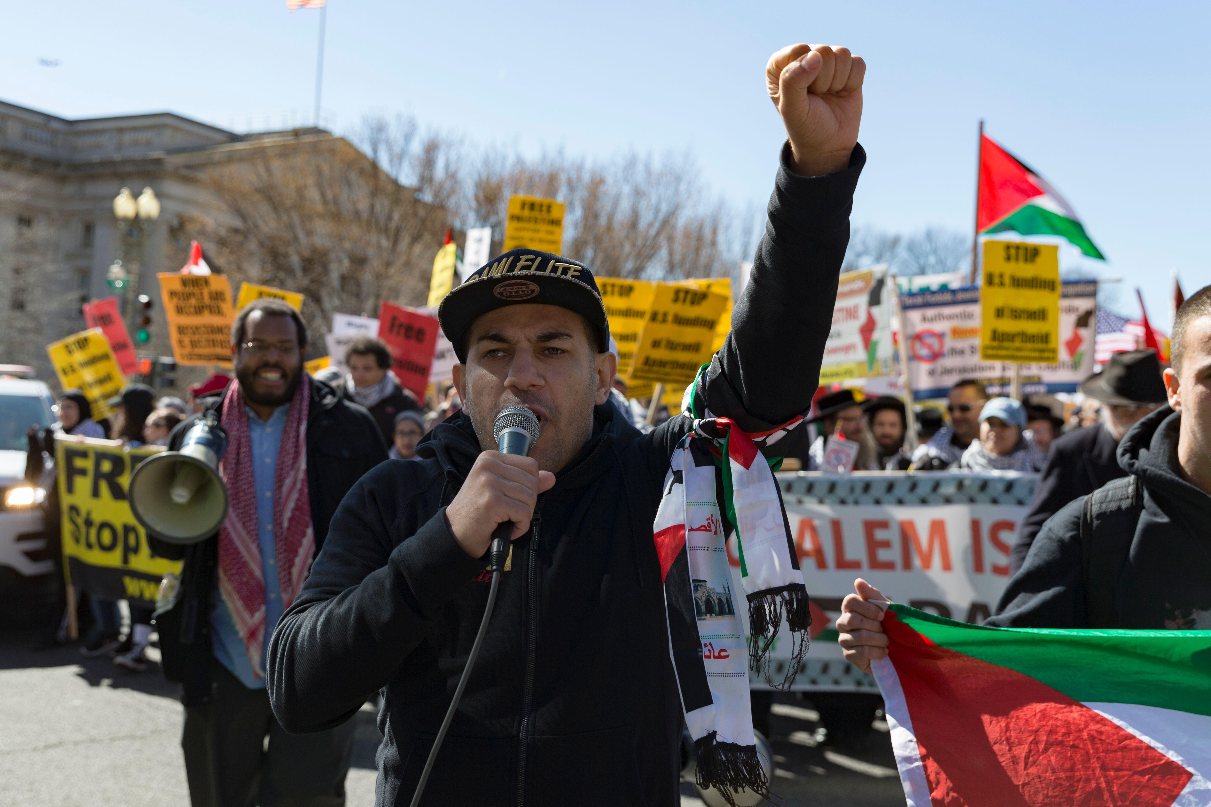 """A demonstrator raises his fist and chants """"free Palestine"""" at a protest. The crowd behind him marches with signs calling for an independent Palestinian state."""