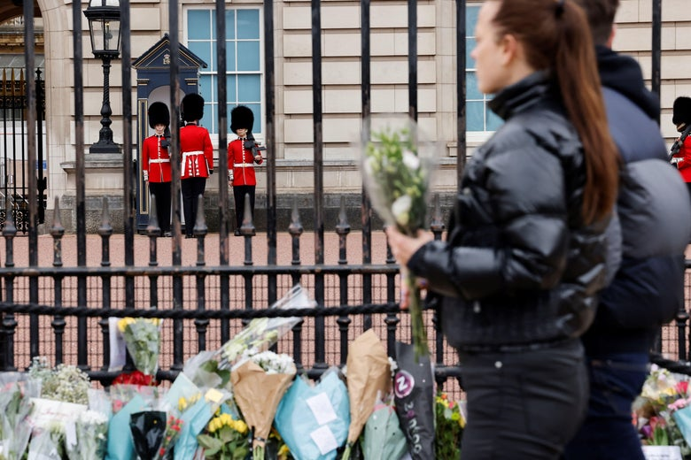 Members of the public line up to lay floral tributes to Britain's Prince Philip, Duke of Edinburgh, outside Buckingham Palace, central London on April 10, 2021, the day after his death at the age of 99.