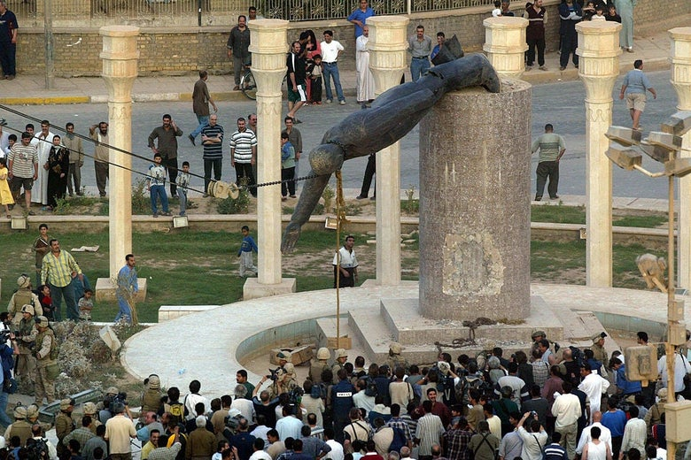 A crowd, seen from above, watches as American soldiers pull a statue of Saddam Hussein off its pedestal with a rope and a chain.