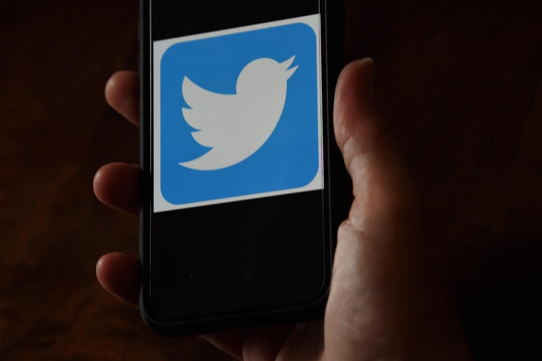 A Twitter logo is displayed on a mobile phone.