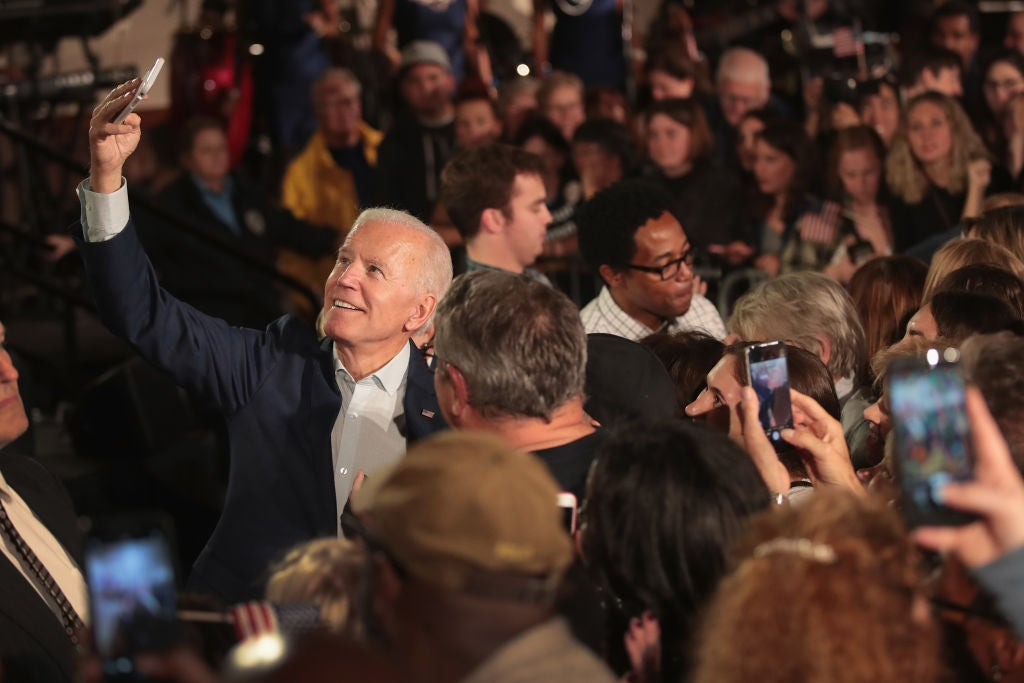 Biden takes a selfie with a fan in a crowd of supporters.
