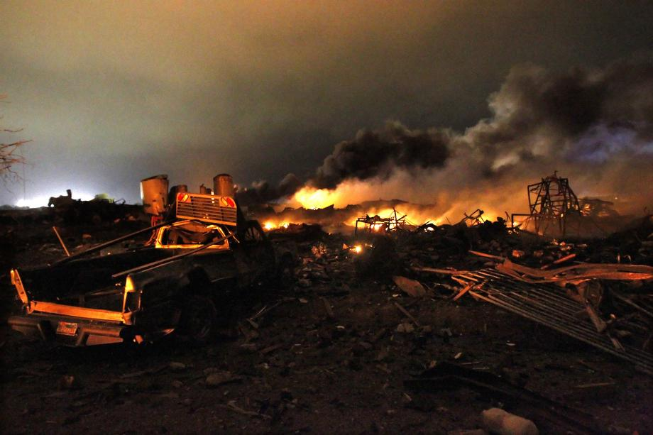 A vehicle is seen near the remains of a fertilizer plant burning after an explosion at the plant in the town of West, near Waco, Texas early April 18, 2013.