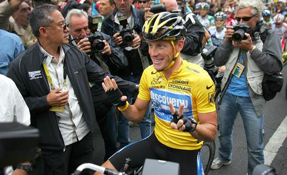 Lance Armstrong of the USA riding for the Discovery Channel team, shows seven fingers (meaning seven victories).