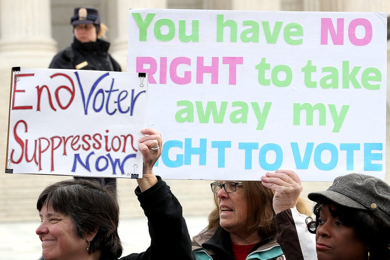"Protesters hold up signs reading, ""End voter suppression now,"" and ""You have no right to take away my right to vote."""