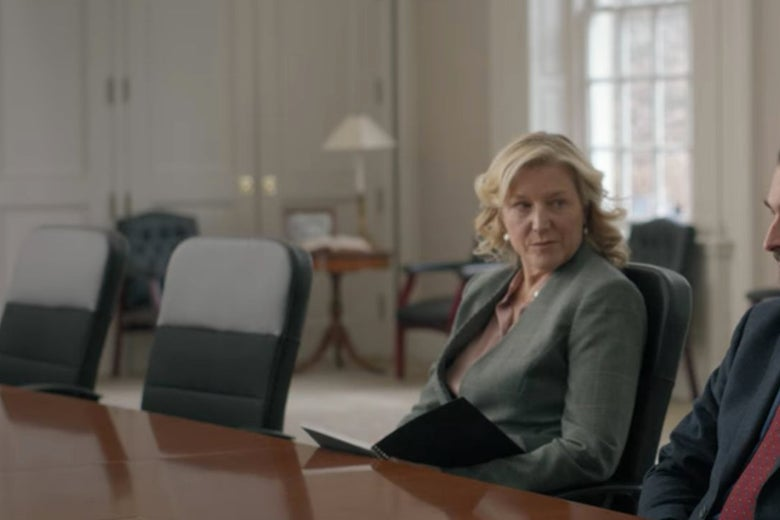 Bill's lawyer at a conference table with some fancy chairs behind her.