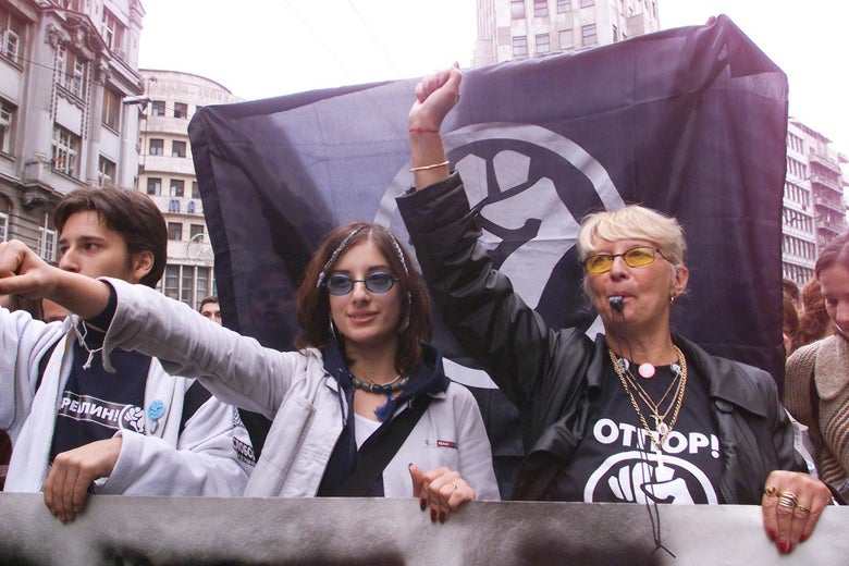 "A young woman and her teacher hold up their fists in front of an ""OTPOR"" flag."