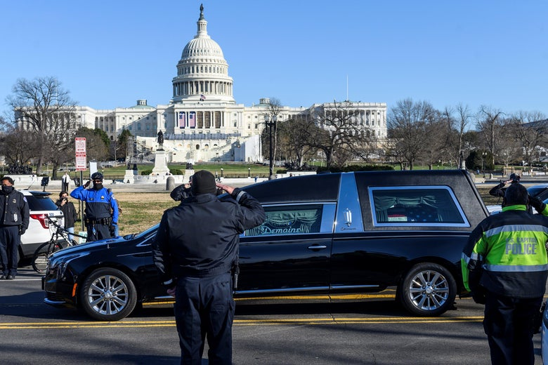 Capitol Police officers salute a hearse passing by on a road in front of the Capitol
