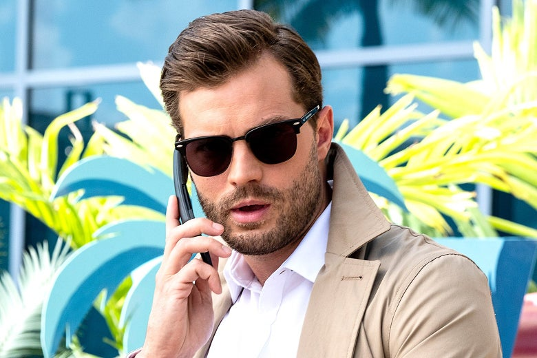 Jamie Dornan wearing a trenchcoat and sunglasses while talking into a phone