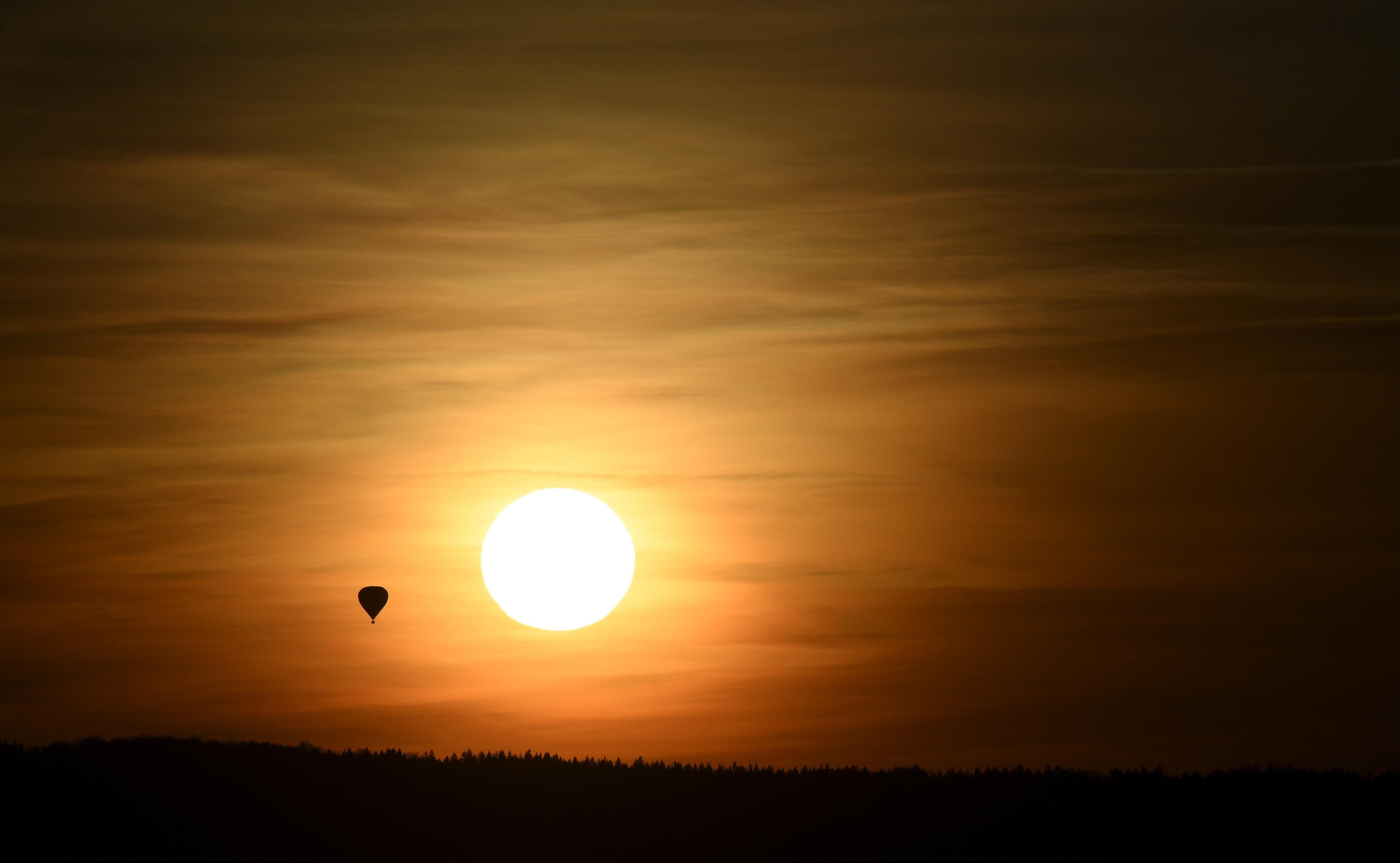 A hot air balloon flies as the sun sets.