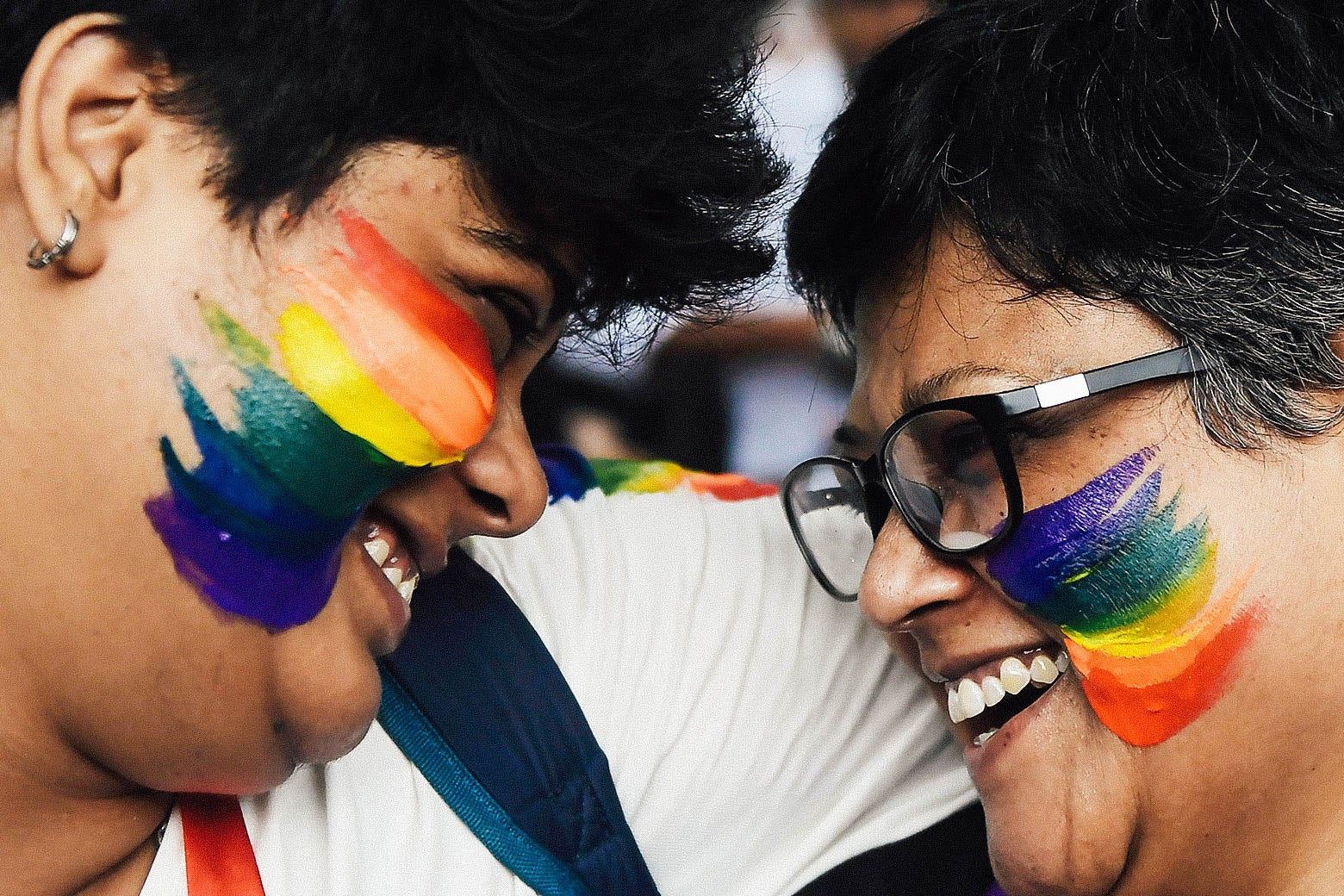 Two Indian supporters of the LGBTQ community celebrate with smiles and rainbow flag face paint on Thursday.