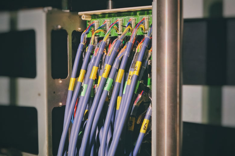 Purple cables are plugged into a router.