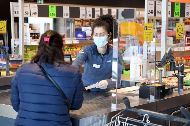 A woman behind a counter wears a mask while helping a customer.