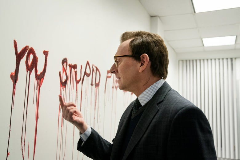 """Michael Emerson, as Leland Townsend, examines red liquid on his finger. The wall in front of him is covered in dripping red letters spelling out """"you stupid pig."""""""