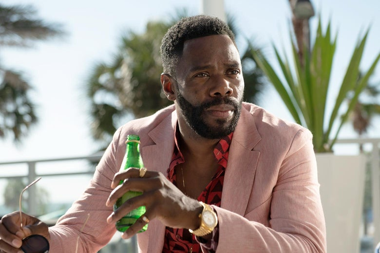 Colman Domingo wearing a pink suit and holding a sparkling water bottle.