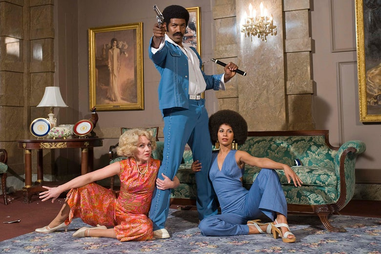 Michael Jai White, wearing a 70s-style mustache, afro, and suit, holds a gun and is flanked by two women holding onto his legs.