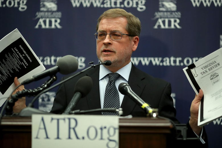 "Grover Norquist, at a lectern with microphones that reads ""ATR.org,"" holds up two packets of paper."