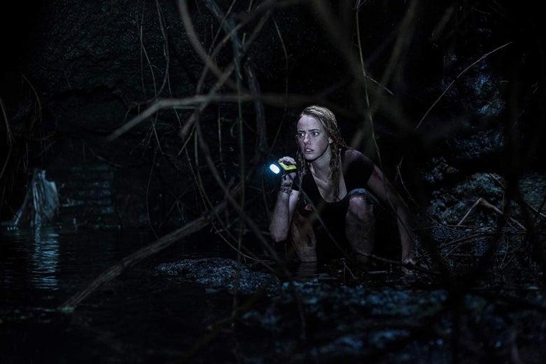 A woman shines a flashlight into dark water.