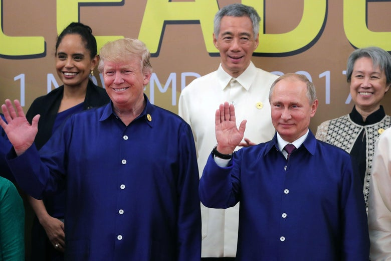 U.S. President Donald Trump and Russian President Vladimir Putin wave during a group photo of APEC leaders