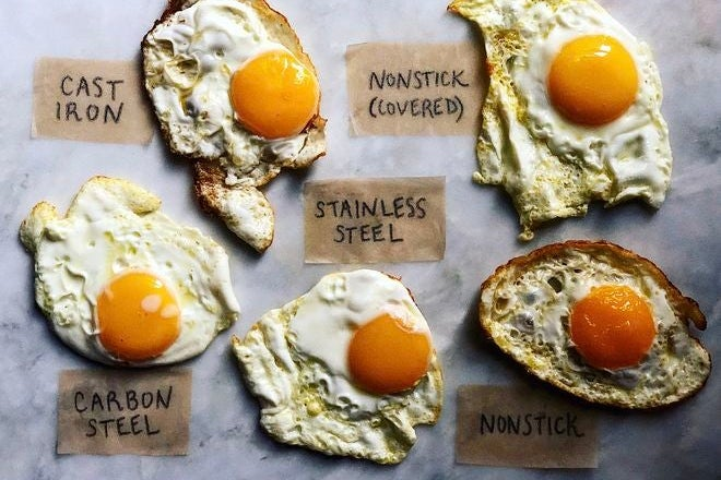 Five fried eggs labeled with type of pan and method they were fried with. Clockwise from top left: cast iron, nonstick (covered), nonstick, stainless steel, carbon steel.