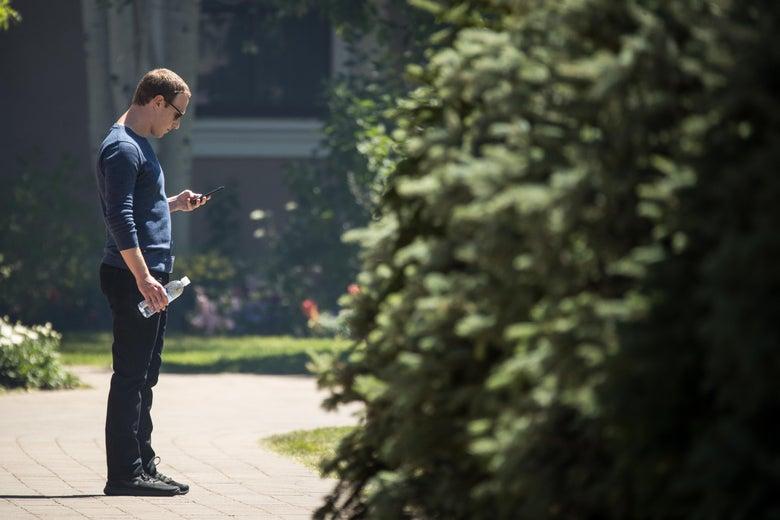 Mark Zuckerberg looking at his phone.