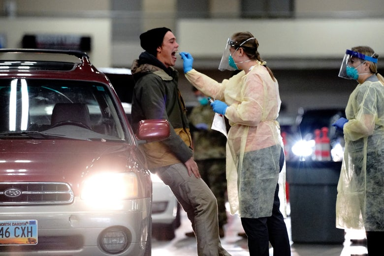 A medical worker in PPE swaps a man's throat as he stands beside a car.