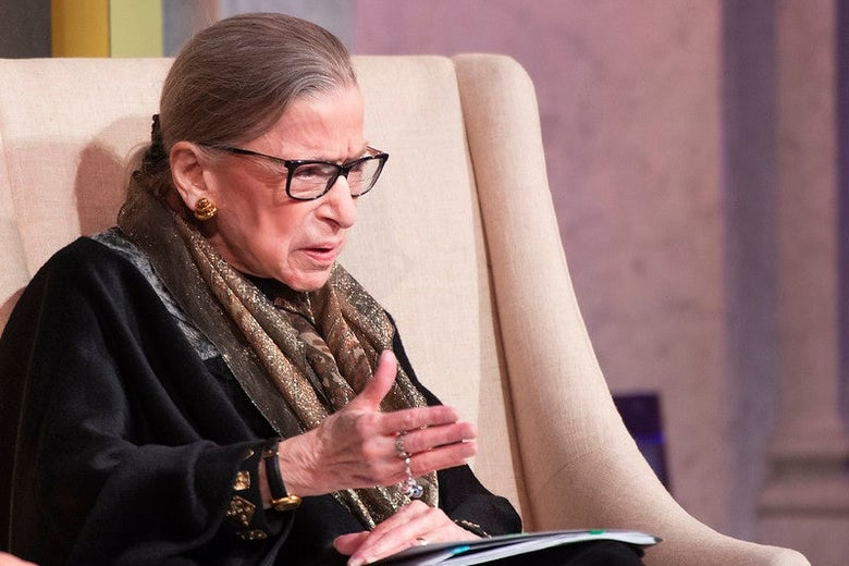 Ginsburg motions with her hand as she speaks seated onstage