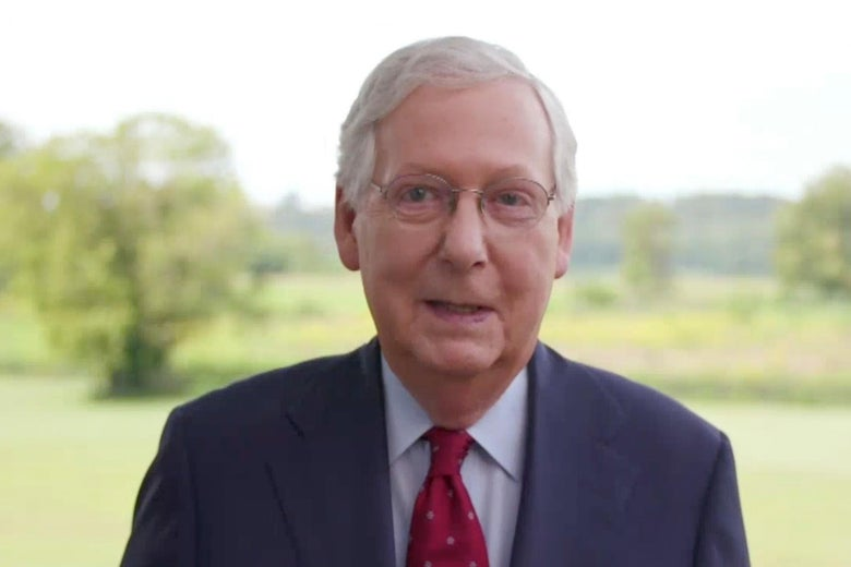 Mitch McConnell speaking into the camera with green landscape behind him.