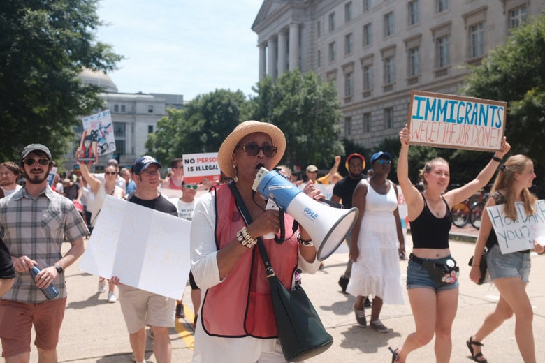 An activist leads a group of demonstrators to the Justice Department doors.