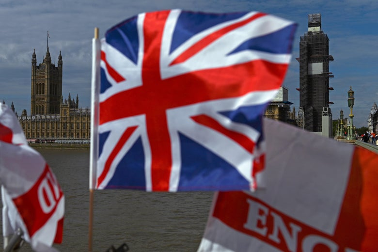The Palace of Westminster with a Union flag in the foreground in central London.