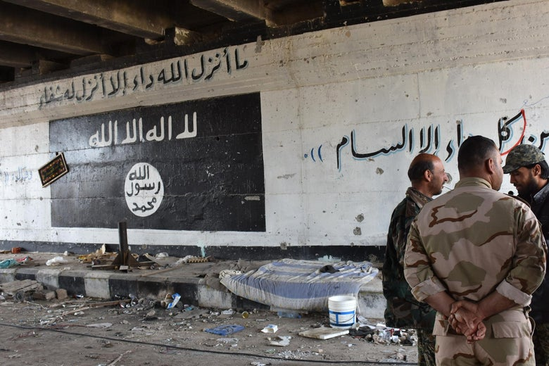 Men stand talking in a tunnel in front of a wall with graffiti of the ISIS flag.