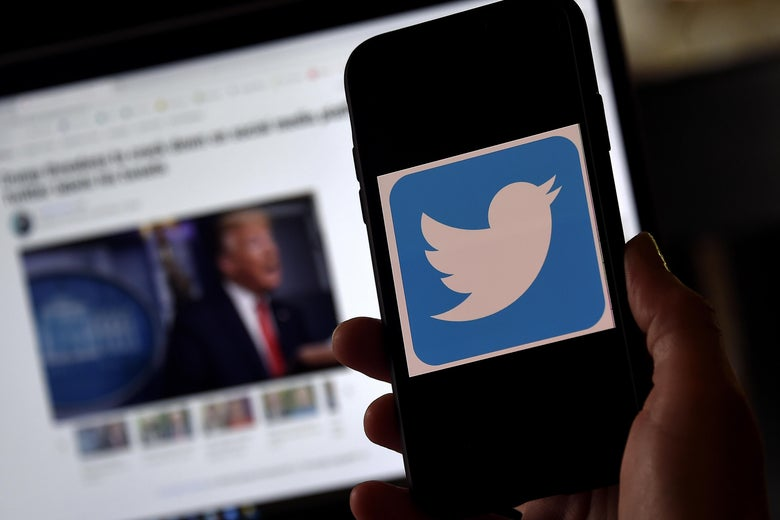 A Twitter logo is displayed on a mobile phone with Donald Trump's Twitter page shown in the background on a desktop screen.