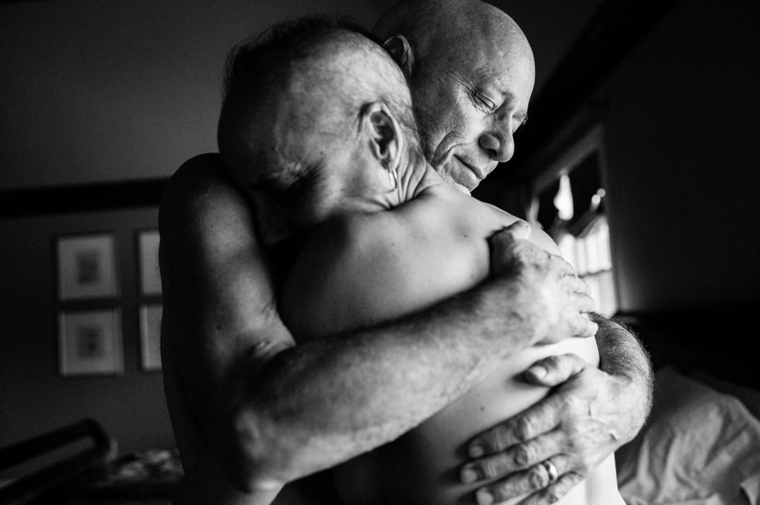 Howie and Laurel Borowick embrace in the bedroom of their home. In their thirty-four year marriage, they never could have imagined being diagnosed with stage-4 cancer at the same time. Chappaqua, New York. March 2013.