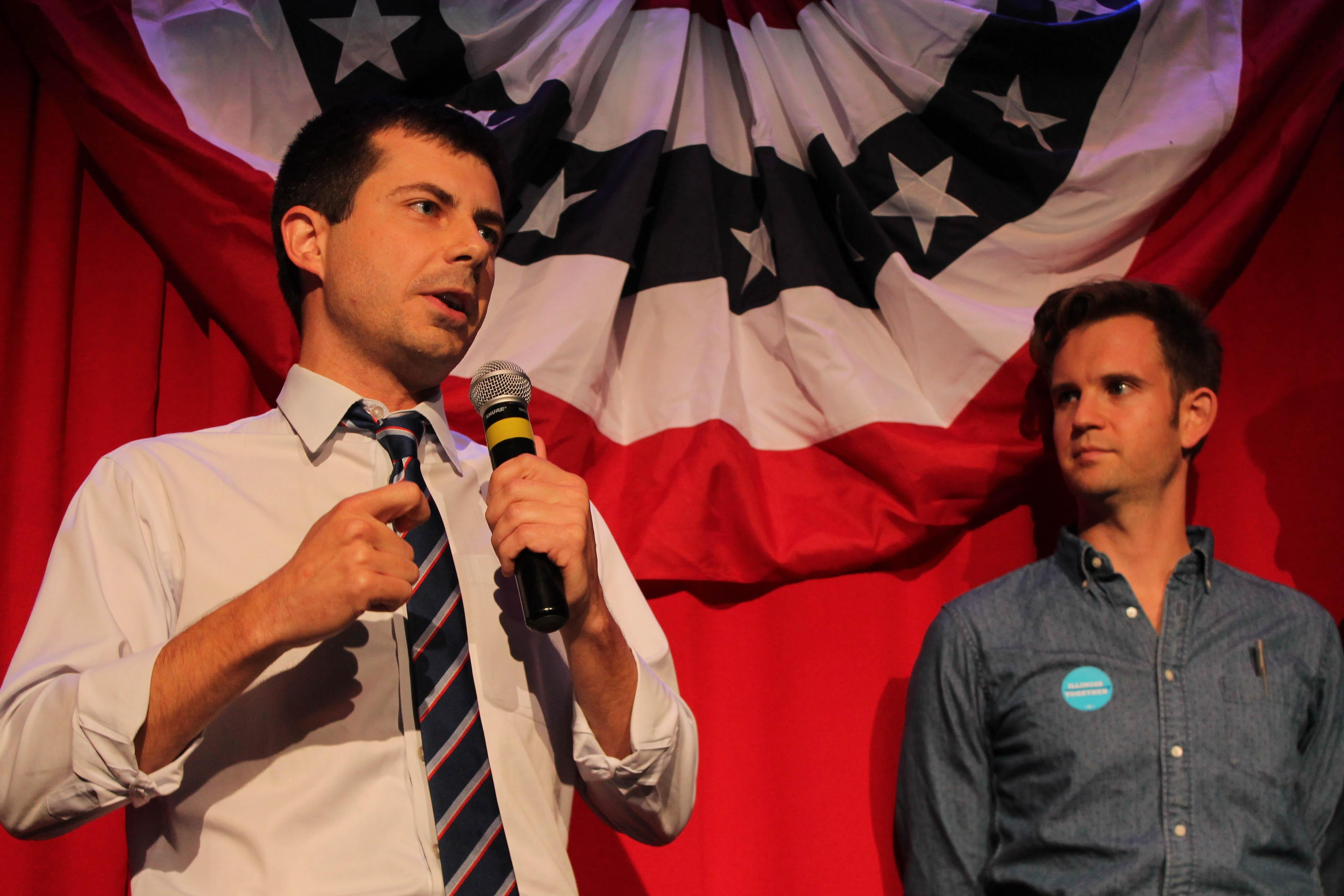 Standing in front of a patriotic-looking background, Buttigieg speaks into a microphone.